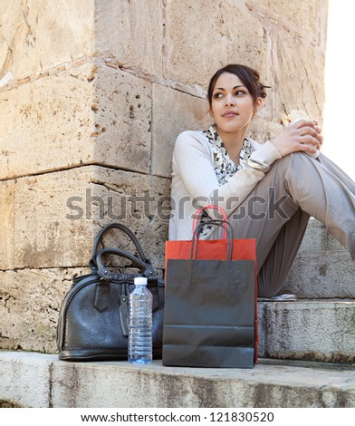 Young businesswoman having a lunch break and eating a sandwich while sitting on stone steps with textured stone walls around her.