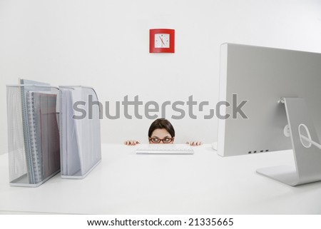 Young businesswoman hiding behind desk. Copy space - stock photo