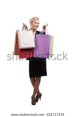 Young businesswoman in a black suit holding shopping bags, isolated on white background