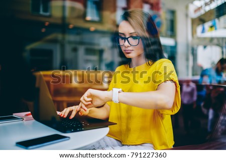 Young businesswoman in eyeglasses looking at display of wristwatch and managing time while checking email on laptop.Freelancer with smartwatch on hand working on article at netbook before deadline