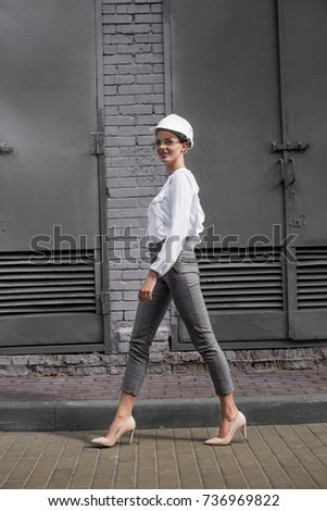 Young businesswoman in formal wear and hardhat walking along grey brick wall