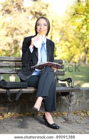 young businesswoman in park having breakfast