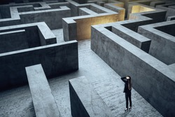 Young businesswoman in suit standing in maze. Business and challenge concept.