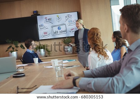 Young businesswoman interacting with colleagues during meeting in board room