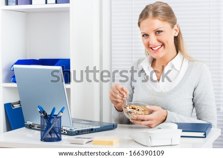 Young businesswoman is eating cereals for breakfast at work,Healthy breakfast