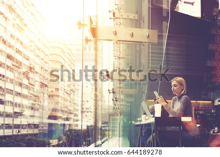 Young businesswoman is reading e-mail on cell telephone, while is sitting in modern coffee shop interior with large buildings outside the window and copy space background for your advertising content
