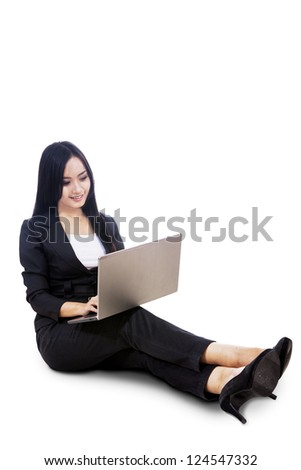 Young businesswoman is sitting with her laptop, isolated on white