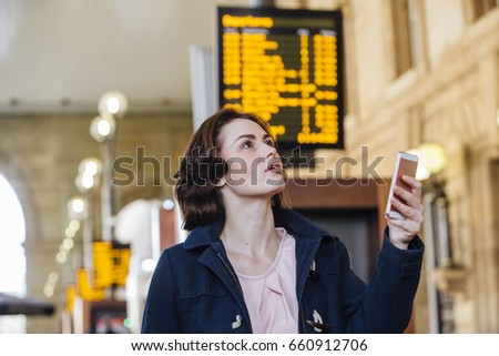 Young businesswoman is using her smart phone to check for her train time on the departure board.