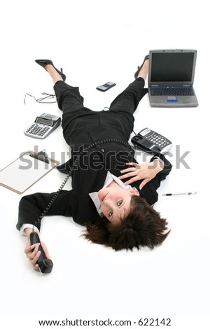Young businesswoman laying on floor among office items.  Clipboard, calculator, laptop, phone, pen, adding machine.  Shot in studio over white.