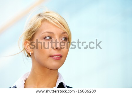 Young businesswoman looking right outside office building