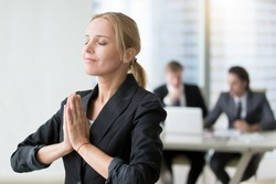Young businesswoman meditating, habits of successful woman, taking care of herself in personal and business life, staying present and cherishing all the good life. Relaxation techniques at workplace