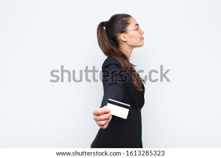 young businesswoman on profile view looking to copy space ahead, thinking, imagining or daydreaming with banknotes with bills