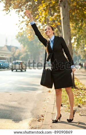 young businesswoman on street trying to hail taxi cab