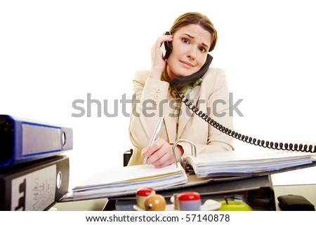 Young businesswoman on two phones taking notes