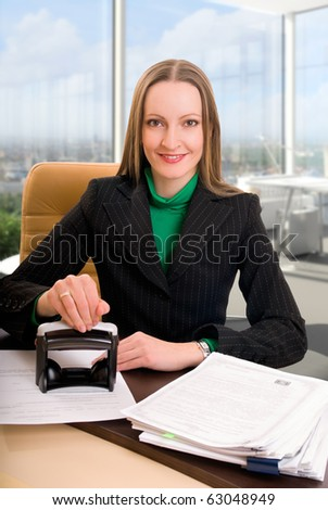 Young businesswoman (or notary public) seating at the desk in office and stamping document