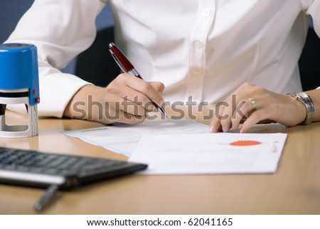 Young businesswoman (or notary public) sitting at the desk in office and signing document