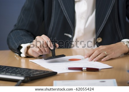 Young businesswoman (or notary public) sitting at the desk in office and stamping document