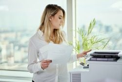 young businesswoman prints on the printer in the office