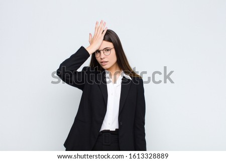 young businesswoman raising palm to forehead thinking oops, after making a stupid mistake or remembering, feeling dumb against white wall