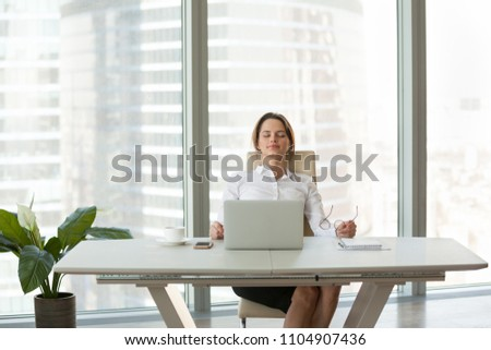 Young businesswoman relaxing leaning on comfortable ergonomic chair in modern office room, calm happy employee feels no stress free relief taking break to rest from computer work breathing fresh air