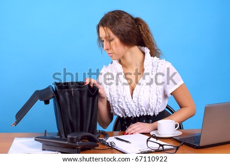 Young businesswoman searching some document in briefcase at the office