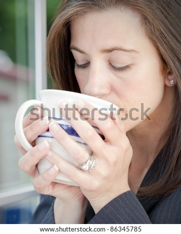 Young businesswoman sipping from a coffee mug