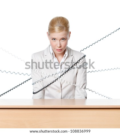 Young businesswoman sitting at a office table tied with phone wire, isolated