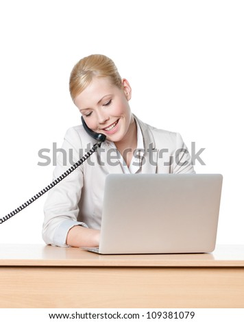 Young businesswoman sitting at a table and talking by phone, isolated