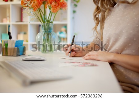 Young businesswoman sitting at desk and working. Beautiful woman signed card