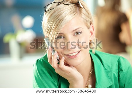 Young businesswoman sitting at desk in office, talking on mobile phone, smiling. - stock photo
