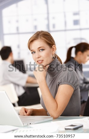 Young businesswoman sitting at desk in office working on laptop, colleagues working in the background.