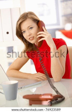 Young businesswoman sitting at office desk, talking on landline phone. Looking at camera.?