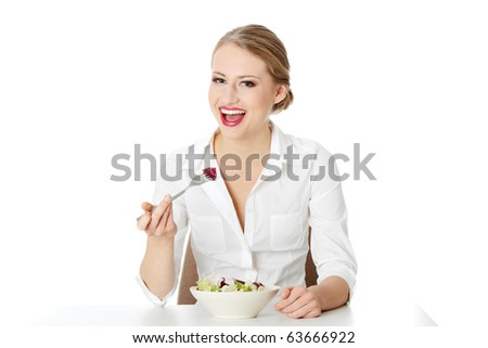 Young businesswoman sitting behind the desk and eating salad isolated on white