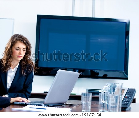 Young businesswoman sitting by meeting table at office in front of a huge blank plasma TV screen and using laptop and phone.