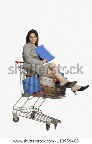 Young businesswoman sitting in a shopping cart with files
