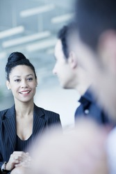 Young businesswoman sitting in business meeting with colleagues