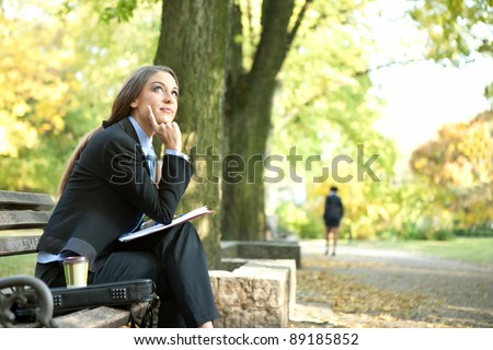 young businesswoman  sitting on bench in park and thinking, outdoor