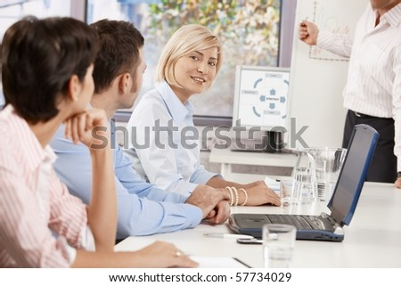 Young businesswoman sitting on business meeting with colleagues in office, looking at camera, smiling.? - stock photo