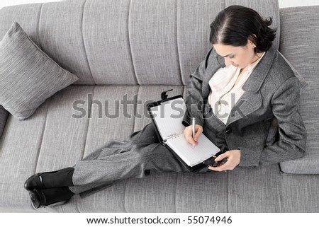 Young businesswoman sitting on sofa, working, overhead view.