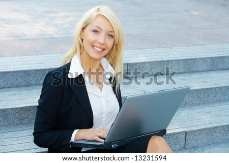 Young businesswoman sitting on stairway, using laptop computer