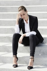 Young businesswoman sitting on steps with head in hands
