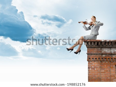 Young businesswoman sitting on top of building and playing violin #198852176