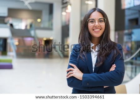 Young businesswoman smiling at camera. Portrait of cheerful Hispanic businesswoman in formal wear standing with crossed arms and looking at camera. Business concept Foto stock ©