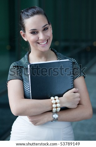 Young businesswoman smiling in front of an office building