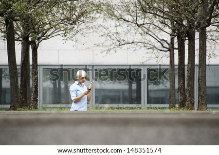 young businesswoman smoking cigarette during break out of office building. Wide shot, copy space