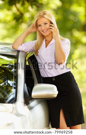 Young businesswoman speaking on mobile phone, leaning against her new car