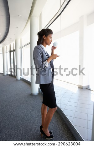 Young Businesswoman Standing In Corridor Of Modern Office Building Drinking Coffee