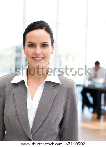 Young businesswoman standing in front of her team while working in the background