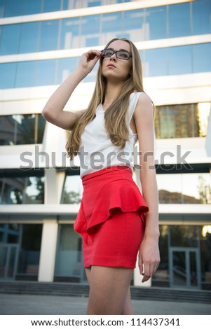 young businesswoman standing in front of office buildings with glasses in her hand