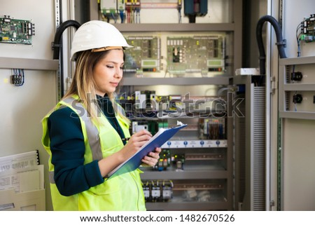 Young businesswoman standing in front of the control panel in the control room #1482670526
